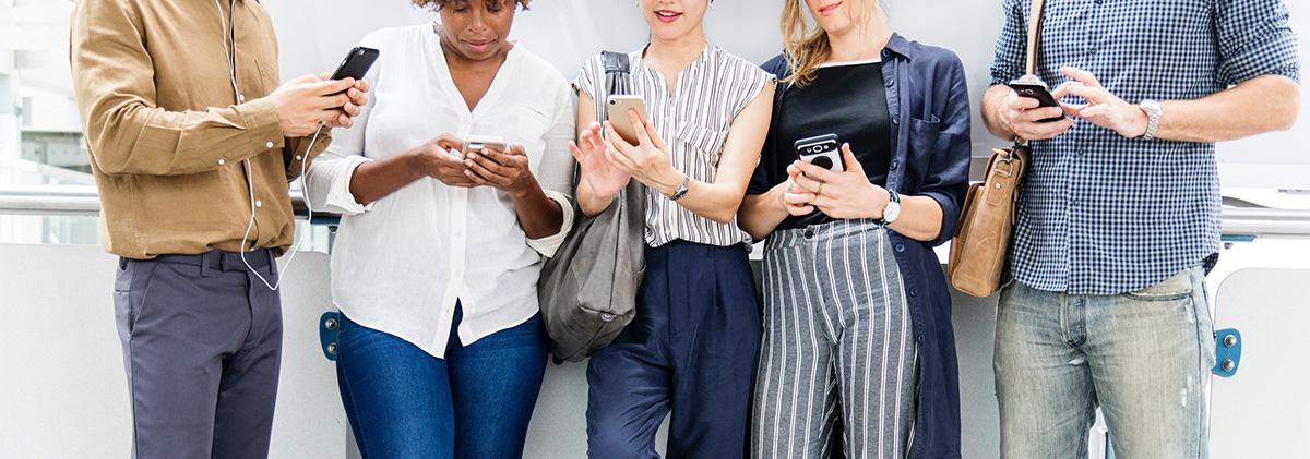 Fem personer av blandat kön står och kollar i sina smartphones