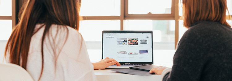 Två kvinnor tittar på en hemsida på en dator