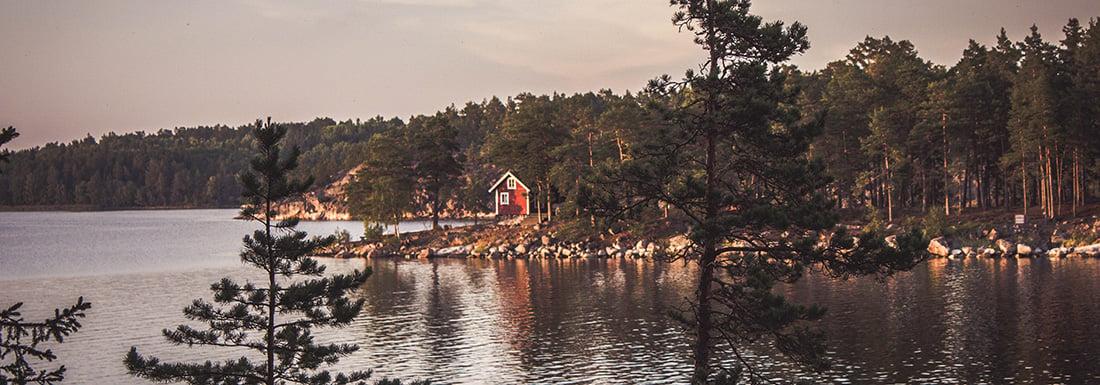 Faluröd stuga vid svensk sjö