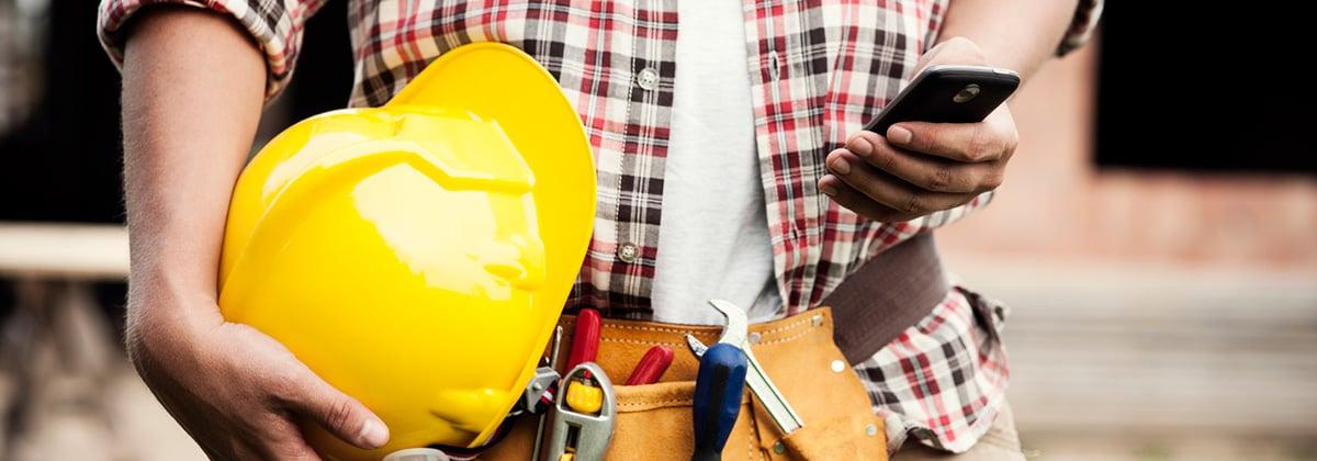 Man på byggarbetsplats kollar sociala medier