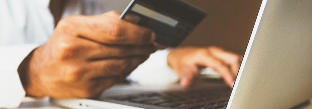 Man använder dator och håller i ett kreditkort