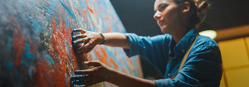 kvinna målar med händerna på stor canvas