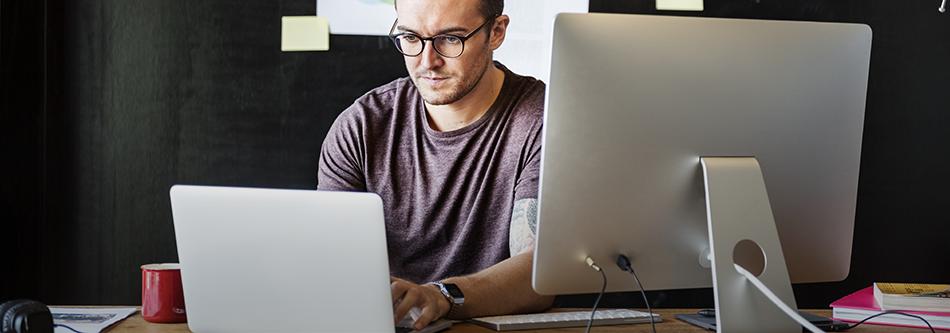 ung man sitter vid dator och skärm