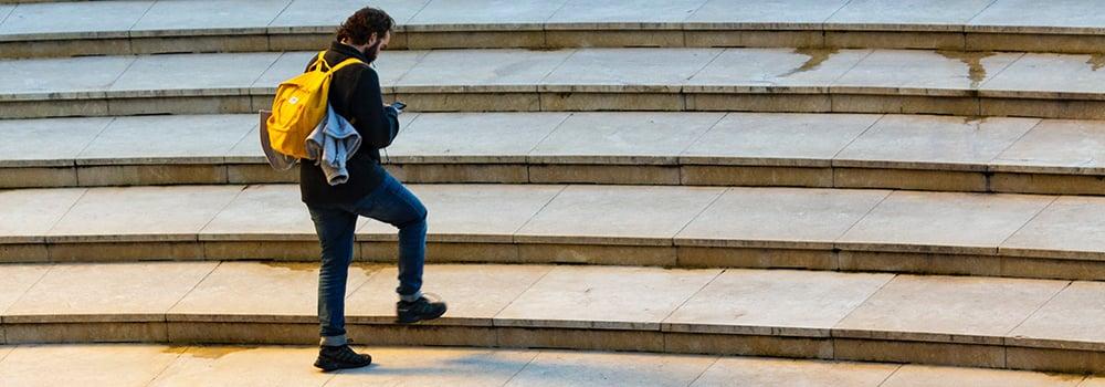 Man med gul ryggsäck går upp för trappor