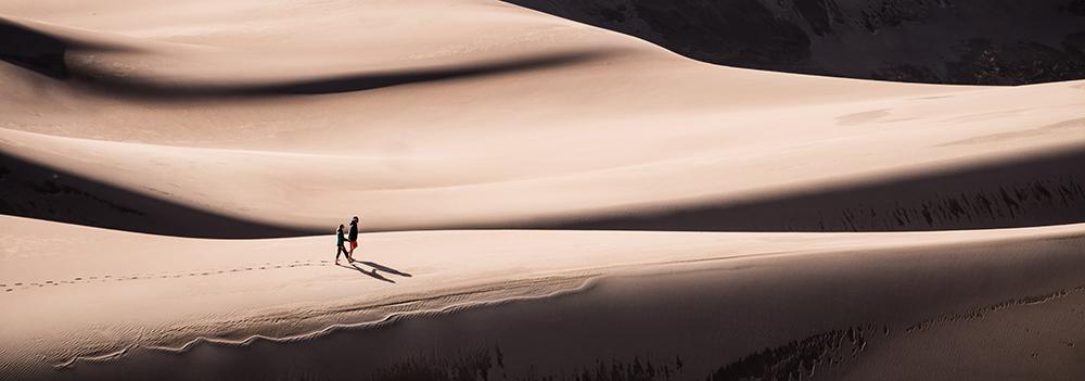Två personer vandrar genom en öken