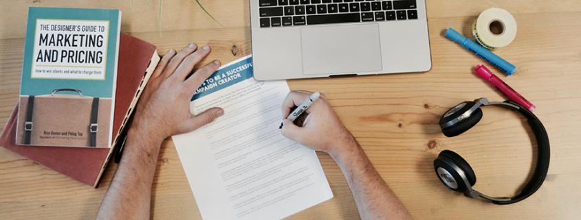 Man skriver på papper intill dator och böcker